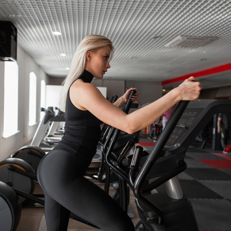 Young beautiful slim woman doing cardio training on a stepper simulator in a modern gym. Girl in training in a sports studio. Concept of sports and health.