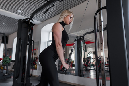 Young woman with a beautiful body in sportswear plays sports in a gym. Girl at workout in fitness studio.