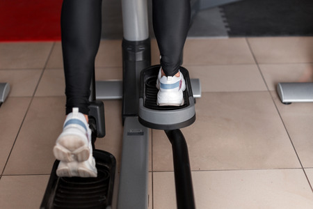 Young woman in black leggings in white sneakers walks on a stepper simulator in the gym. Girl does cardio to burn calories. Close-up of womans legs. Back view. Stock Photo