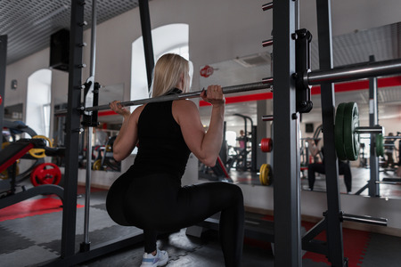 Young woman with a beautiful body doing heavy exercises in the gym with a metal fingerboard. Girl in great shape doing squats in a fitness studio. Side view. Stock Photo