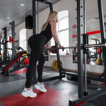 Beautiful young woman blonde in sportswear with a beautiful slim body is standing near a metal simulator in a fitness studio. Girl is engaged in fitness in the gym.