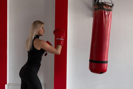 Young female boxer in red boxing gloves in motion to hit a punching bag. Girl is training in the gym. Boxing concept. Fitness training.