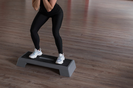 Young slim woman in sporty leggings in a black top in training in a gym crouches using a platform step. Girl coach shows exercises. Morning fitness. Close-up