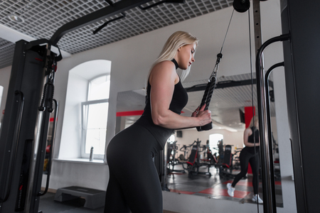 Young woman in black sportswear is doing strength exercises for hands in modern gym. Girl goes in for sports. Healthy lifestyle. Side view. Stock Photo