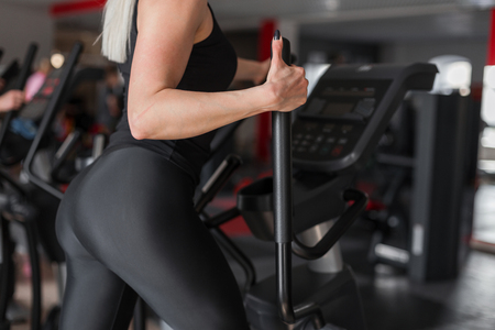 Young woman athlete with a beautiful sexy body is engaged on a modern simulator in the gym. Girl in training. Close-up of womans body and simulator.