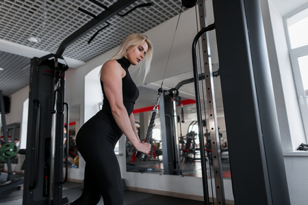 Attractive young woman blonde in sportswear doing strength exercises for hands with the help of modern simulator in the fitness studio. Girl is training in the gym. Stock Photo