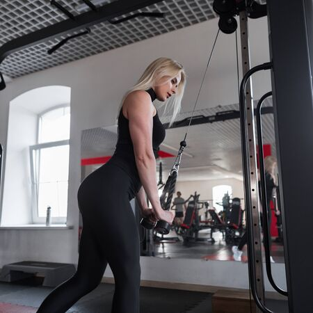 Woman in black sportswear is training in the gym. The concept of beauty and health.