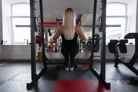 Young woman with a beautiful body is doing hand exercises in a modern gym. Girl goes in for sports indoors. Concept of health and beauty. Back view.