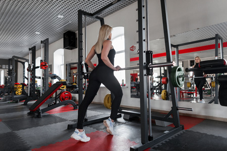 Slim young woman blonde in a stylish sports t-shirt in black leggings in white sneakers deals with fitness in the gym. Athletic girl indoors. Back view.