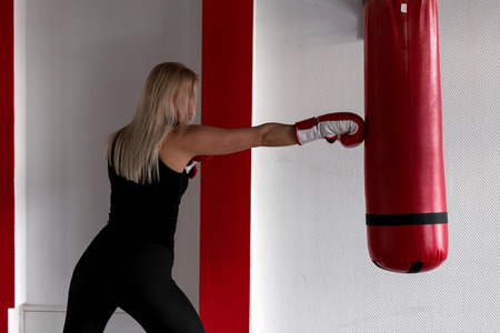 Concentrated blond woman in red boxing gloves in black sportswear doing boxing training with a punching bag. Girl in the boxing gym beats a punching bag.