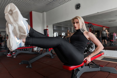 Slim athletic young woman in training in the gym. Girl is engaged in the sport room.
