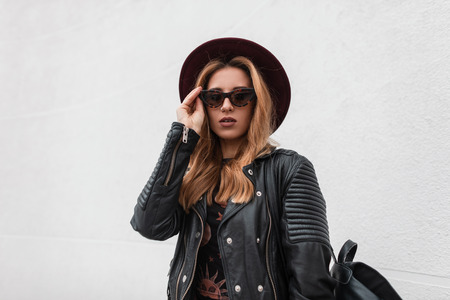 Portrait of a redhaired sexy young hipster woman in an elegant hat in dark sunglasses in a trendy leather jacket with a backpack with an earring in nose outdoors near white wall. Modern urban girl. Stock Photo