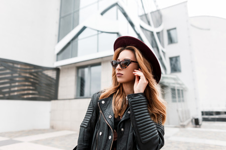 Gorgeous red-haired hipster young woman in vintage sunglasses in a stylish hat in a fashionable black leather jacket posing near a modern building in the city. Beautiful urban girl. Women's fashion. 写真素材