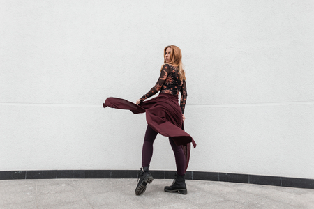 Modern pretty young woman in a fashionable patterned blouse in trendy purple pants in vintage black shoes with a cape poses near a white wall in the city. Attractive red-haired girl model outdoors.