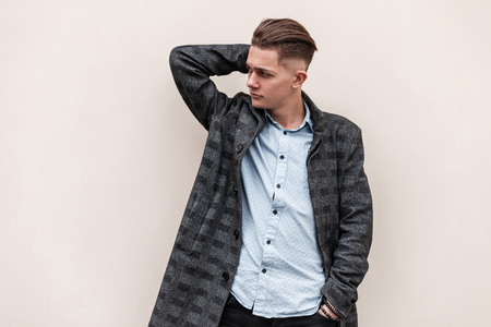 Stylish handsome young man in a plaid elegant jacket in a trendy shirt with a stylish hairstyle in jeans posing near a white vintage wall in the city. Attractive urban guy model outdoors.