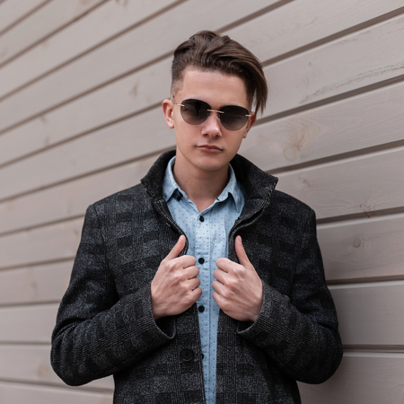 Serious handsome young hipster man in trendy sunglasses in a plaid jacket in an elegant shirt with a fashionable hairstyle stands near a vintage wooden wall in the city. Nice guy enjoying the weekend.