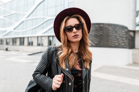 Portrait of a redhaired attractive young hipster woman in an elegant hat in trendy sunglasses in a black leather jacket with a backpack with an earring in nose outdoors in the city. Modern urban girl.