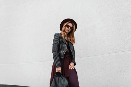 Young beautiful hipster woman in trendy sunglasses in a black jacket with a leather backpack in pants in an elegant hat is standing near a white wall outdoors. Attractive red-haired girl relaxes.