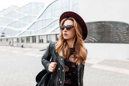 Gorgeous red-haired hipster young woman in dark sunglasses in an elegant hat in a stylish black leather jacket with a trendy backpack in the city near a modern building.European pretty girl for a walk