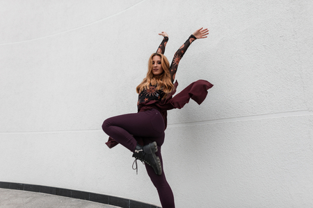 Fashionable pretty young woman with red hair in a stylish blouse in trendy pants with a purple cape in black leather shoes dancing near a white wall in the spring day. European girl model outdoors. Stock Photo