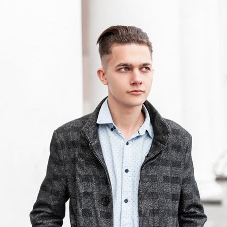 Nice handsome young man in a gray plaid elegant jacket in a shirt with a stylish hairstyle stands near a white vintage building with columns in the city. Elegance guy fashion model. Trendy menswear.