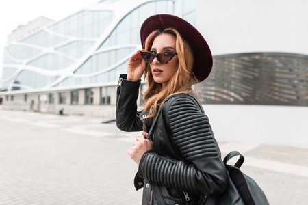Pretty young hipster woman in an elegant purple hat in stylish sunglasses in a black leather jacket with a fashionable backpack travels around the city near a modern building. European girl outdoors. 版權商用圖片