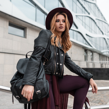 Young pretty attractive woman in black leather jacket in pants with a stylish backpack in an elegant hat posing sitting near a modern building in the city. Fashionable red-haired girl enjoys vacation.