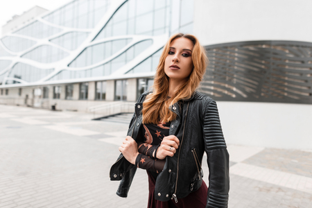 Pretty European young woman with an earring in nose in a vintage leather jacket in a stylish patterned blouse standing outdoors in the city. Red-haired urban girl walks down the street. Spring fashion