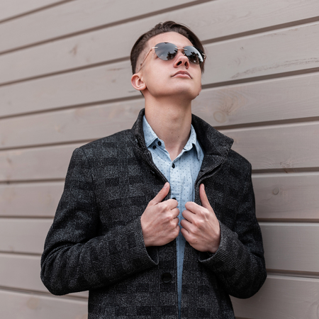 Handsome young hipster man with stylish hairstyle in trendy dark sunglasses in an elegant gray jacket in a vintage shirt enjoys a spring day near a wooden building. Modern guy model relaxes outdoors. Foto de archivo - 122969145