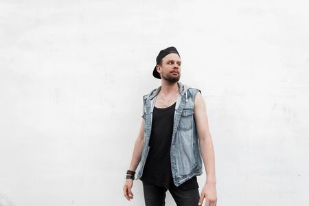 American young man hipster in a T-shirt in a denim vest in jeans in a fashionable black cap with a beard is standing near a white vintage wall on a warm summer day. Nice guy model outdoors. Menswear. Foto de archivo - 125231833