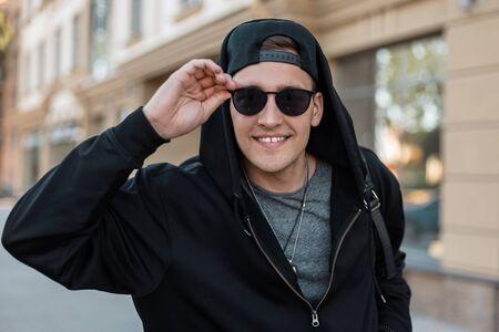 Happy handsome young hipster man in stylish sunglasses in a fashionable sweatshirt with a backpack in a cap is standing and smiling near a vintage building on the street. Joyful guy outdoors. Stock Photo