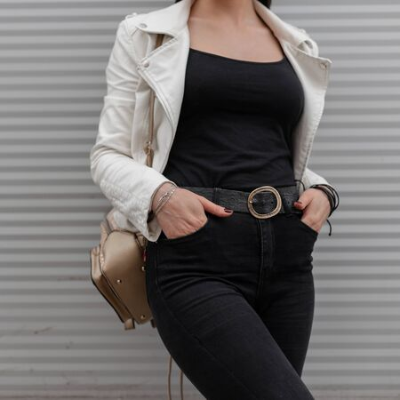 Young woman in white leather jacket in a t-shirt in black jeans with a stylish golden backpack poses near the modern wall. Details of everyday look. Fashionable women's modern clothing. Close-up. Stock Photo