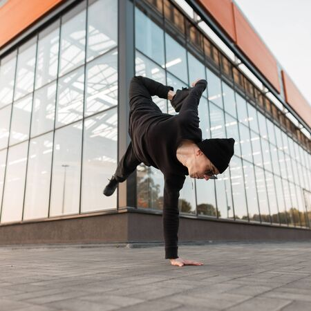 Nice young professional man dancer in black stylish clothes in a knitted hat in stylish sunglasses is doing a handstand near a glass modern building. Cool hipster guy dancing outdoors. Street style. Foto de archivo - 125232193
