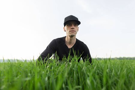 Stylish young man in a black shirt in a black trendy cap rests sitting in the green grass in the field. Nice guy enjoying a weekend in nature outdoors. Stock Photo