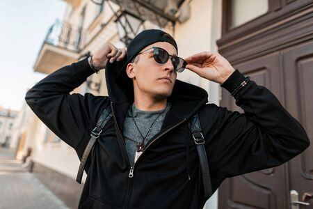 American young hipster man in stylish black clothes in a trendy cap in sunglasses with a stylish backpack walks around the city on a sunny summer day. Attractive urban guy model enjoys the weekend. Stock Photo