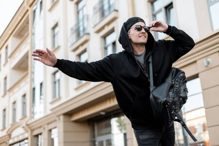 Urban cheerful young man hitchhiker in a cap in trendy sunglasses with a stylish backpack in a black sweatshirt is standing in the city and trying to catch a taxi. Happy guy trying to catch the car.