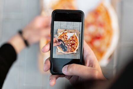 Young man makes a photo of delicious pizza on a smartphone. Closeup of male hands and pizza image on screen.  Top view.