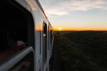 Beautiful landscape of countryside at sunset. View from the train window on a bright orange summer sunset. Concept of travel by train and adventure.