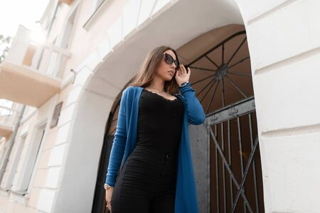 Modern hipster young woman in a fashionable long knitted cape in a stylish black top in black jeans in trendy sunglasses walks near a vintage building in the city. European girl resting outdoors. Stock fotó