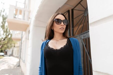 Pretty elegant modern young hipster woman in stylish sunglasses in a trendy top with lace in a blue knitted cape stands in a city near a vintage building on a bright summer day.Beautiful girl outdoors