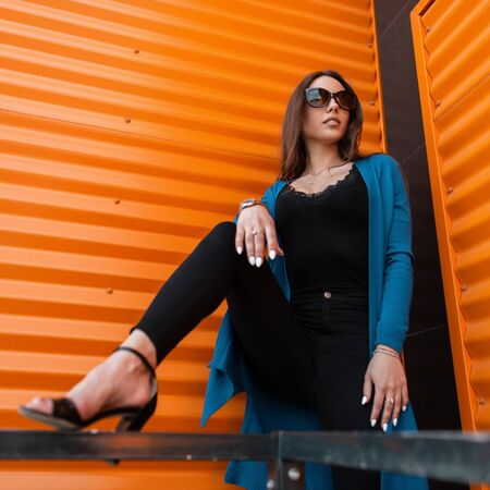 Pretty young hipster woman in stylish clothes in trendy sunglasses in trendy sandals poses near the modern orange metal wall in the city on a summer day. Attractive urban girl fashion model outdoors.