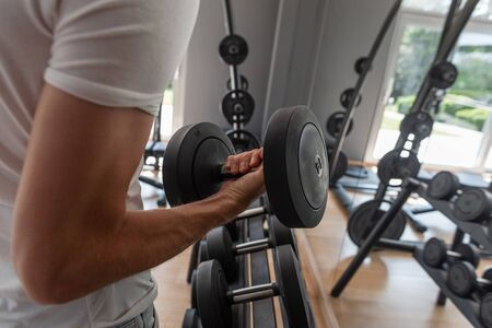 Young sports man in a white trendy T-shirt picks up a dumbbell. Guy is training in the gym. Close-up of a mans hand with dumbbell.