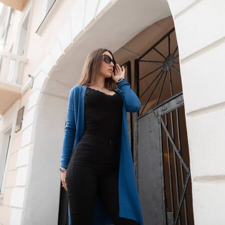 Stylish beautiful young hipster woman in sunglasses in a black T-shirt in a knitted summer cape in vintage jeans is standing near a vintage building with an iron gate in the city. Urban girl walks. Stock fotó
