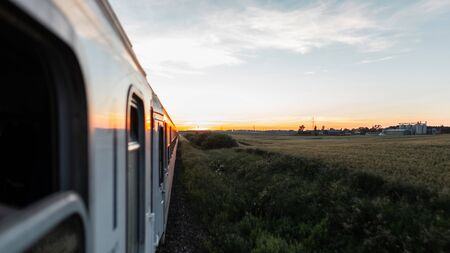 The view from the train window overlooking the wagons on the field and the orange summer sunset. Imagens