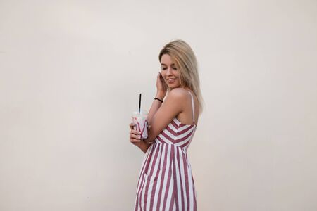 Beautiful positive pretty young woman with a cute smile in a trendy pink summer dress with stripes with a milky sweet cocktail stands near a white vintage wall. Attractive joyful girl relaxes outdoors
