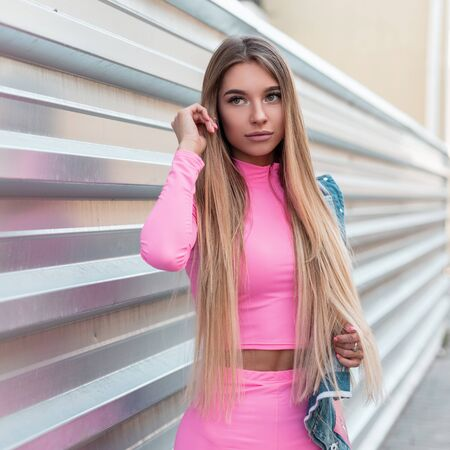 Beautiful glamorous young woman with long hair in a fashionable pink summer tracksuit with a denim jacket stands near a silvery wall on a street in the city. Urban sweet girl relaxes outdoors. Summer. Stock fotó
