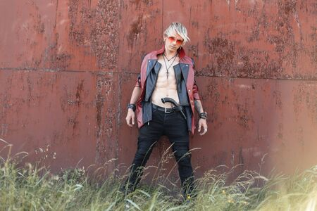 Old-fashioned young hipster man with blond hair in a glasses in a red-black leather jacket in jeans with old weapons poses near a rusty wall on a bright summer day.Sexy guy with a torso outdoors