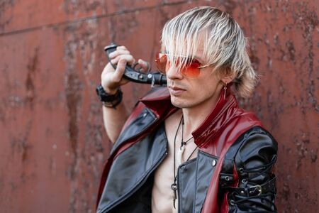 Cool young blond man with a naked torso in a fashionable red-black leather jacket in red glasses posing near an old rusty building. Handsome sexy hipster guy with a vintage gun. Future punk style Foto de archivo - 126647204