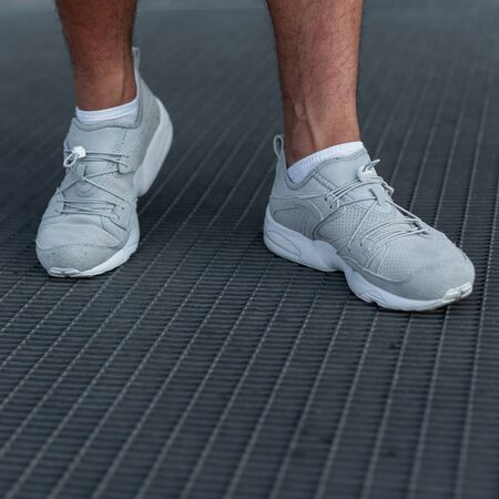 Mens legs in sports fashionable white sneakers. Stylish casual look. Details of everyday look. Mens trendy sneakers. Street fashion. Close-up.