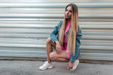 Pretty beautiful woman with blond long hair in summer trendy clothes in white stylish sneakers posing sitting in a city near a silvery metal wall. Attractive girl resting on the street. Retro style.
